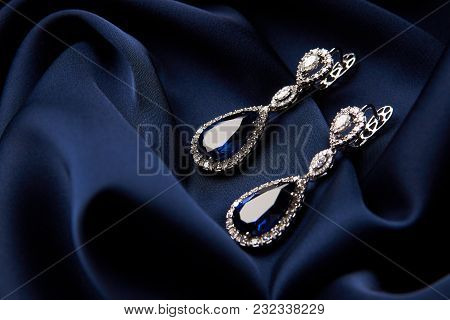 Pair Of Platinum Earring With Sapphire On Blue Satin Background. Luxury Female Jewelry, Close-up