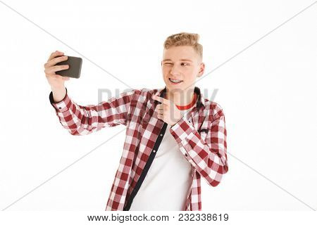 Young guy with braces and playful look pointing finger on camera like cool guy while taking selfie on mobile phone isolated over white background