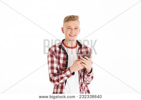 Modern teenager in casual t-shirt 17y wearing braces holding cell phone and browsing or typing using internet isolated over white background