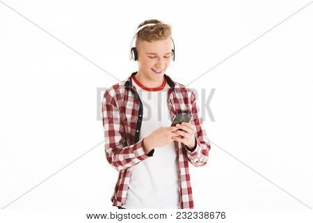 Attractive guy in casual t-shirt 17y wearing braces listening to favorite tune via wireless headphones and using modern gadget isolated over white background