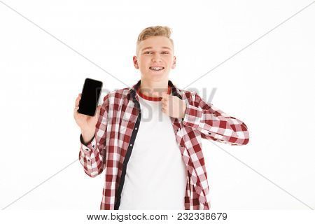 Portrait of a happy schoolboy pointing finger at blank screen mobile phone isolated over white background