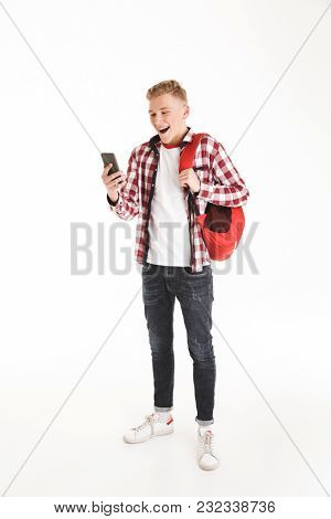 Full length portrait of an excited schoolboy in eyeglasses with backpack using mobile phone isolated over white background