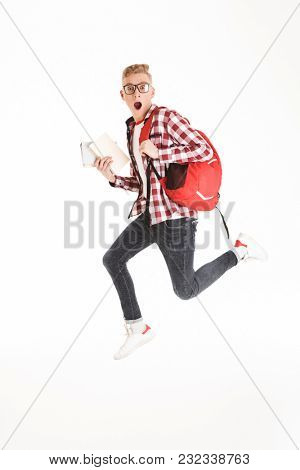 Full length portrait of a shocked schoolboy in eyeglasses with backpack holding books and jumping isolated over white background