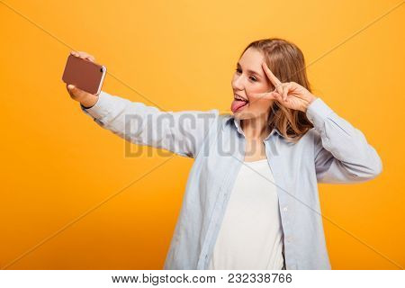 Portrait of a cheery young girl with braces taking a selfie with mobile phone isolated over yellow background