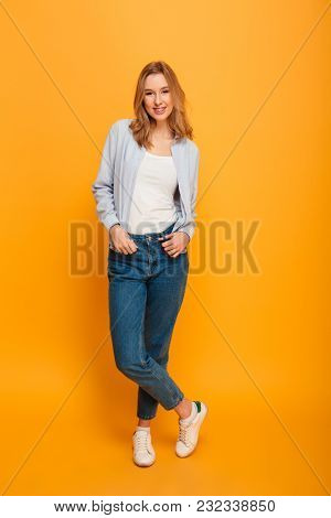 Full length portrait of young woman smiling and posing on camera with hands in pockets wearing casual jeans isolated over yellow background