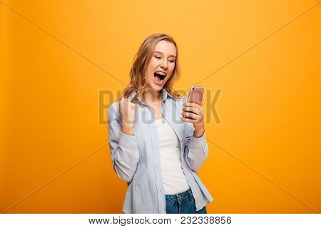 Portrait of a satisfied young girl with braces holding mobile phone isolated over yellow background