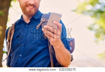 A Happy Handsome Bearded Male Tourist In Casual Clothing Using A Phone.