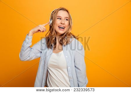 Photo of satisfied smiling woman 20s wearing braces in casual clothing listening to music using wireless earphones isolated over yellow background