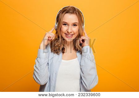 Picture of pretty caucasian woman wearing braces in casual clothing looking on camera while enjoying melody via modern headphones isolated over yellow background