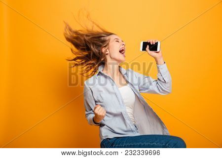 Portrait of a cheerful young girl with braces holding mobile phone and celebrating isolated over yellow background
