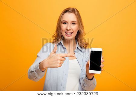 Portrait of a smiling young girl with braces pointing finger at blank screen mobile phone isolated over yellow background