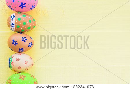 Happy Easter! Row Colorful Easter Eggs With Colorful Paper Flowers On Bright Yellow Wooden Backgroun