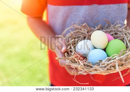 A Kid Holding Colorful Of Easter Eggs In Nest On Grass Green Background.