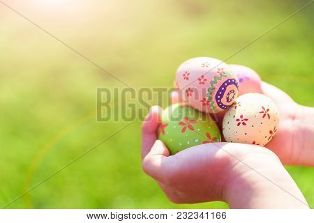 Happy Easter! Close Up Of Little Kid Holding Colorful Easter Eggs On Green Grass Field Background.