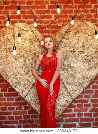 Charming Elegant Woman In A Red Dress On A Background Of A Golden Heart In The Studio
