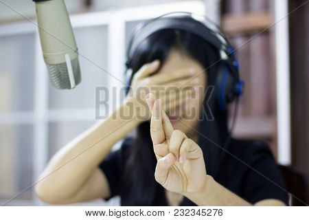 Microphone In Studio With Blurred Asian Women Do Finger Symbol Of Lie