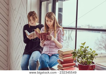 Two Young Student Female Reading Books In A Home.