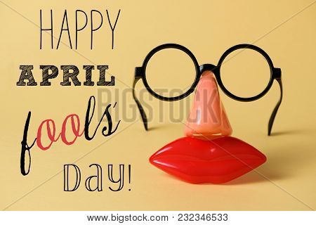 a pair of fake eyeglasses, with nose and mouth, and the text happy april fools day, on a yellow background