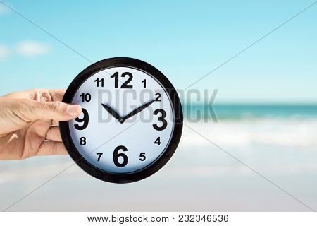 closeup of a young caucasian man with a clock in his hand on the beach, with the ocean in the background and some blank space around it