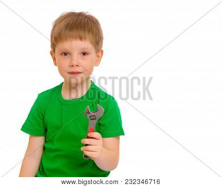 A Cute Little Boy Is Holding A Wrench In His Hand. The Concept Of Development Of Creative And Techni