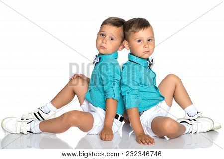 Two Cute Little Boys, Brothers Sit On The Floor In A Studio On A White Background. The Concept Of A