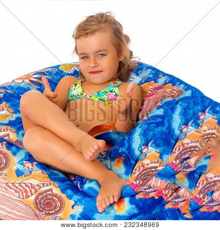 A Nice Little, Tanned Girl In A Swimsuit Resting On A Soft Pillow. The Concept Of Summer Family Vaca