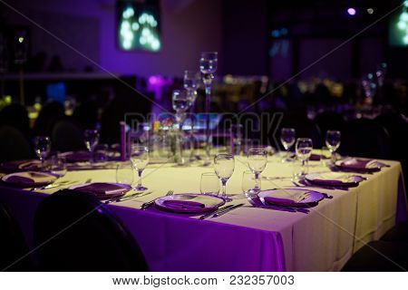 A Table With A White Tablecloth In The Banquet Hall With A Blue Backlight.