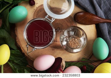 Natural Red Dye For Easter Eggs With Colored Eggs Around On A Wooden Background