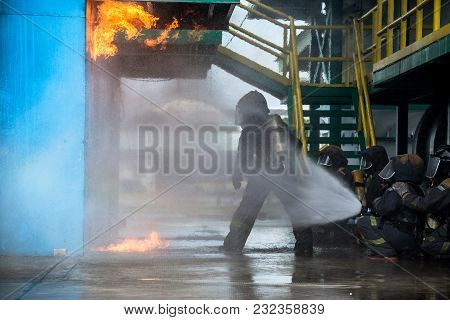 Firemen Using Water From Hose For Fire Fighting At Firefight Training Of Insurance Group. Firefighte