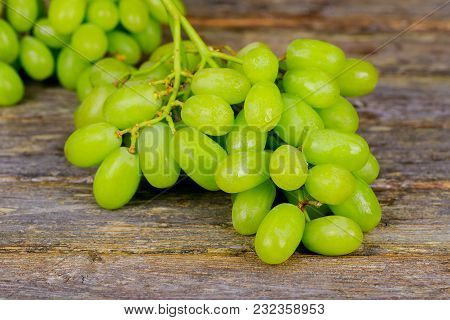 White Grapes On A Wooden Board Grapes With Leaves A Close-up On The Board