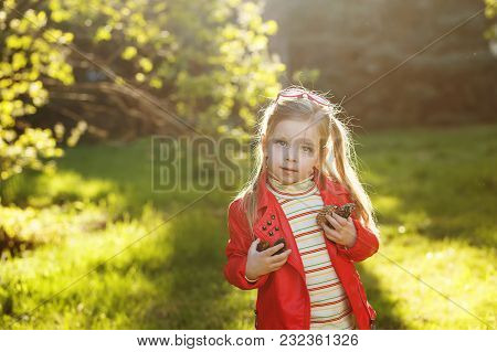 Little Girl Is Holding Bumps. She Walks In The Spring Park. Happy Childhood. Backlight