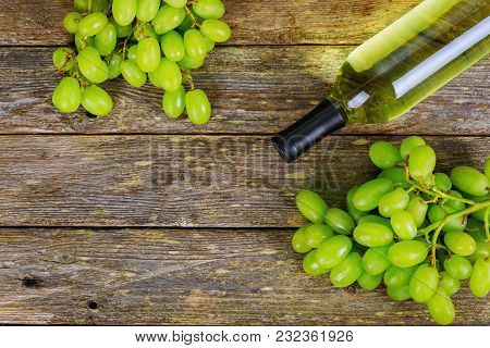 White Wine And Grapes Wine And Grapes In Vintage Setting With Corks On Wooden Table