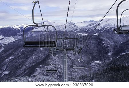Ski Station In The Mountains. There Is A Cable Car For Skiers. The Tops Of The Snow-capped Mountains