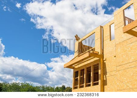 New Residential Building Under Construction On Blue Sky Background. Low Rise Wooden Framework Of The