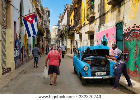 HAVANA,CUBA - MARCH 18,2018 : Street scene with cuban flags, old car and decaying buildings in Old Havana