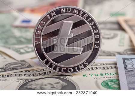 Cryptocurrency Coin Litycoin On The Euro And Dollar Banknotes. Close Up With Selective Focus.