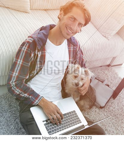 handsome guy with laptop hugging his dog and sitting near the co