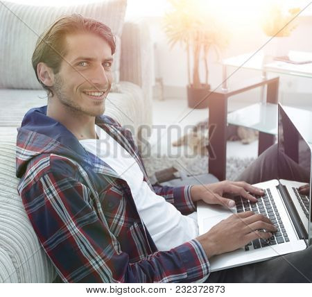 smiling guy with a laptop sitting on the floor near the sofa