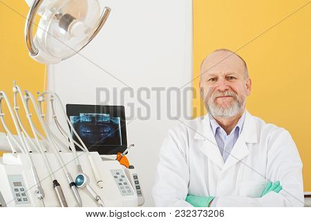 Cheerful Mature Male Dentist Smiling At The Camera In Dental Office