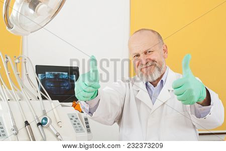 Cheerful Mature Male Dentist Smiling At The Camera In Dental Office Showing Thumbs Up