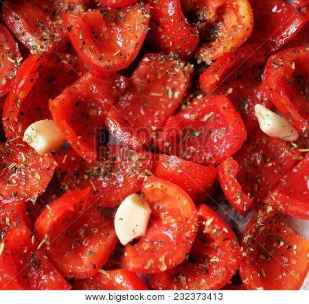 Tomatoes lie on a baking sheet, ready to bake. Sun-dried tomatoe