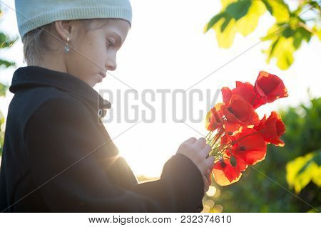 Beautiful Little Girl In Hat And Coat With Orange Poppies In Hands Backlit By Sunset Warm Light
