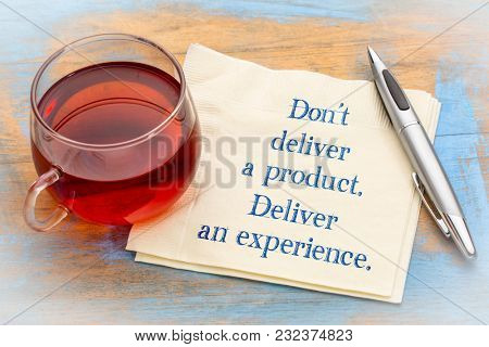 Don't deliver a product. Deliver an experience. Handwriting on a napkin with a cup of tea