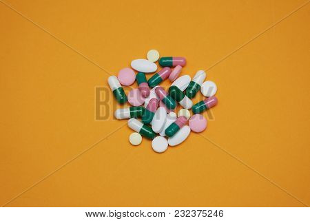 Colored Pills, Tablets And Capsules, Pharmacy And Medicine, On Yellow Background. Healthy And Medici