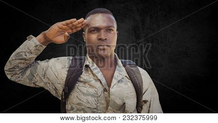 Digital composite of Soldier with backpack saluting against black grunge background
