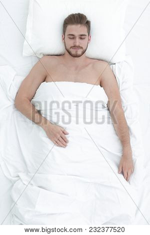 Young man relaxation on the bed top view