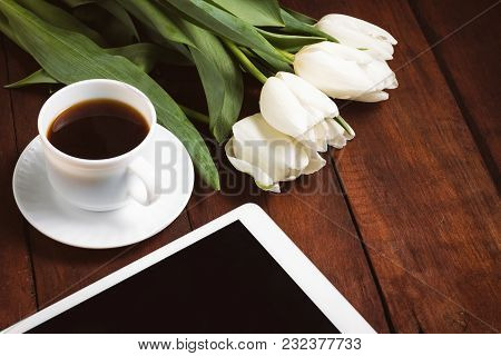 White Tulips, A Cup Of Coffee And A Tablet On A Dark Wooden Background. Concept Of Spring