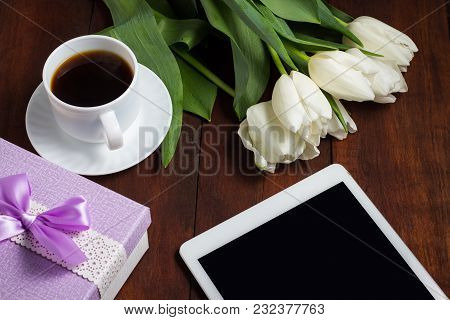 White Tulips, A Cup Of Coffee And A Gift On A Dark Wooden Background. Concept Of Spring