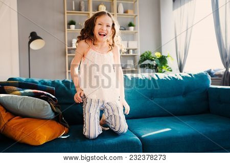 Happy Kid Girl Playing At Home In Weekend Morning And Jumping On Couch In Modern Scandinavian Interi