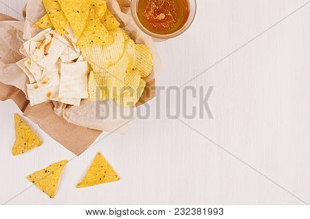 Heap Different Crispy Golden Snacks On Craft Paper, Triangles Nachos, Lager Beer In Glass On Soft Wh